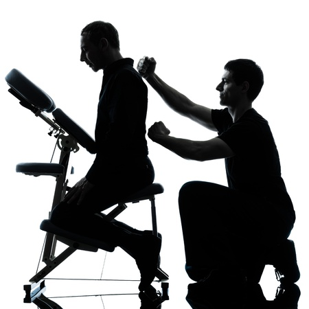 two men performing chair back massage in silhouette studio on white background photo