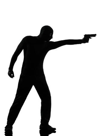 hombre disparando: ladrón criminal terrorista hombre apuntando la pistola en el estudio de la silueta aislado en el fondo blanco