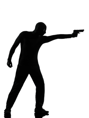 terrorism: thief criminal terrorist man aiming gun in silhouette studio isolated on white background