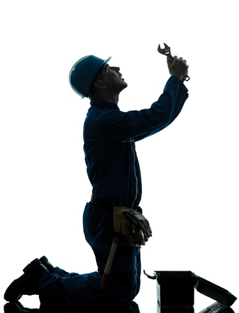 kneeling man: one caucasian repairman worker despair praying silhouette in studio on white background