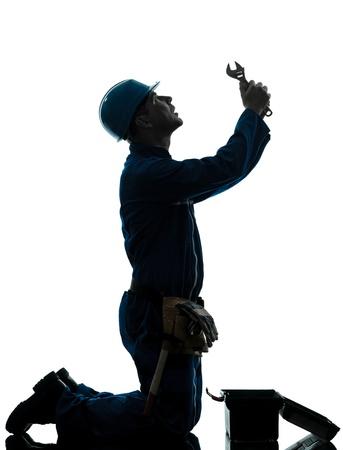 arrodillarse: un reparador cauc�sico desesperaci�n trabajador orando silueta en estudio en el fondo blanco Foto de archivo