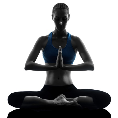 yoga girl: one caucasian woman exercising yoga meditating sitting hands joined in silhouette studio isolated on white background