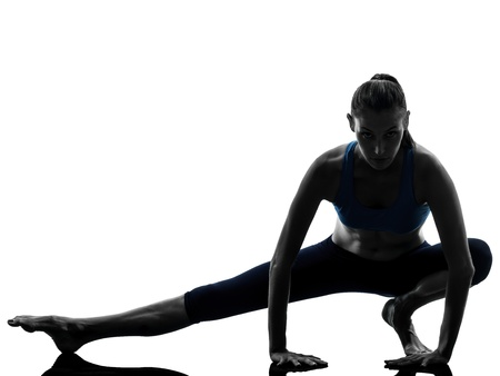 squats: one caucasian woman exercising yoga stretching legs warm up in silhouette studio isolated on white background