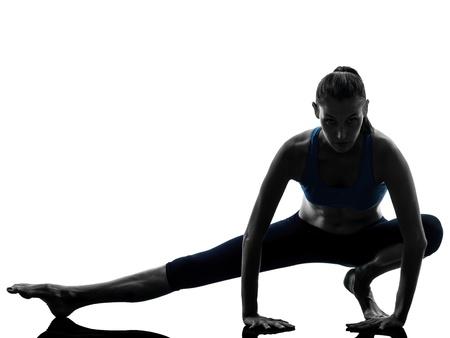 stretching: una mujer cauc�sica ejercicio de yoga estiran las piernas en calor en estudio silueta aislados sobre fondo blanco Foto de archivo