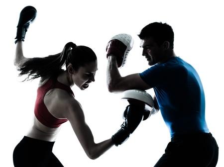 パーソナル トレーナーの男性コーチとボクシングを行使女性のシルエットの白い背景で隔離のスタジオ