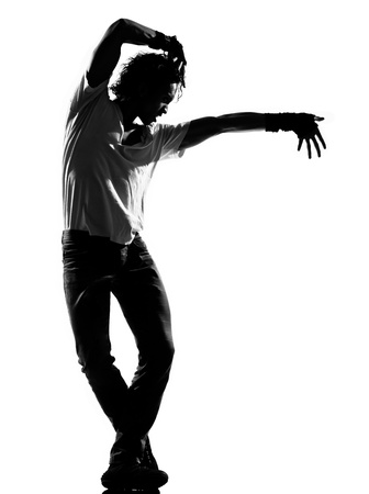 moves: full length silhouette of a young man dancer dancing funky hip hop r&b on  isolated  studio white background