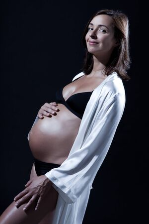 beautiful smiling caucasian pregnant  woman portraitt  in nightie on studio isolated black background Stock Photo - 16713772