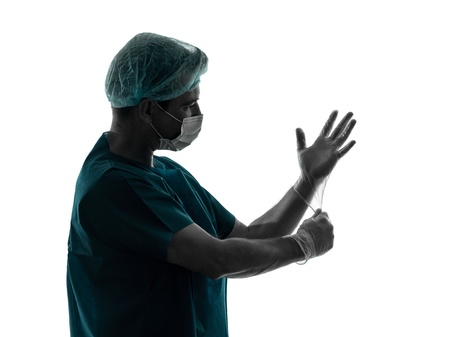 one caucasian doctor surgeon man  latex gloves portrait with face mask medical worker silhouette isolated on white background photo