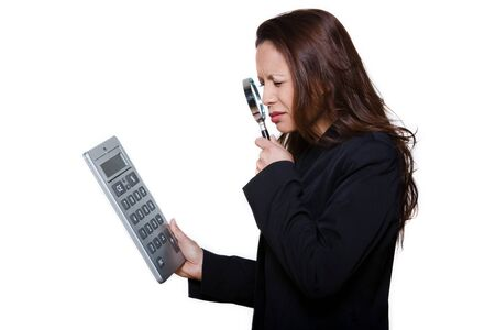 visually: Portrait of visually handicapped woman using magnifying glass to see large calculator isolated on background
