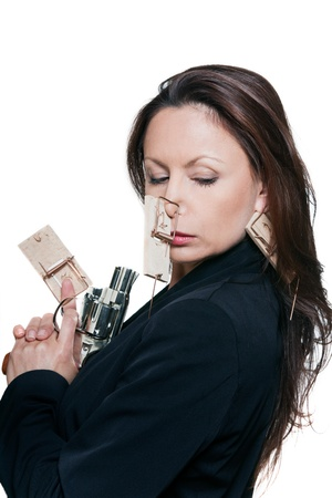 Portrait of beautiful woman with mousetraps holding revolver in studio isolated on white background photo