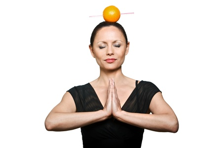 Portrait of beautiful Asian woman with orange on head and hands joined in studio isolated on white background photo