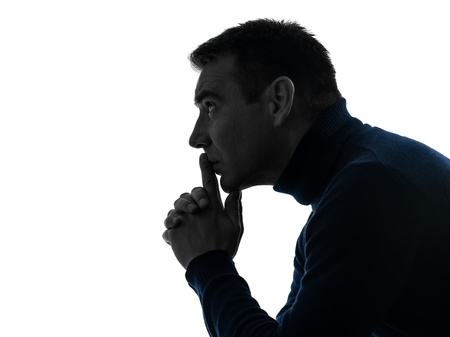 causasian: one causasian man serious thinking pensive portrait in silhouette studio isolated on white background Stock Photo