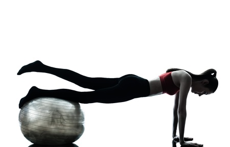 pushups: one caucasian woman exercising fitness ball in silhouette studio isolated on white background