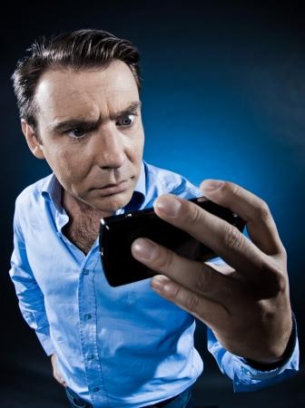 desconfianza: hombre caucásico buscando en el estudio de retrato teléfono enojo aislado sobre fondo negro Foto de archivo