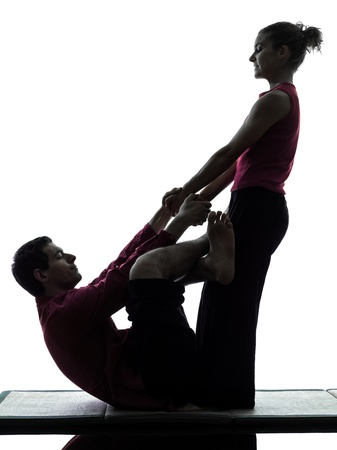 one man and woman perfoming thai massage in silhouette studio on white background Stock Photo - 16827333