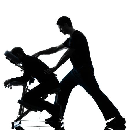 homme massage: deux hommes effectuant un massage du dos chaise en studio silhouette sur fond blanc