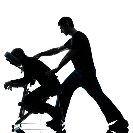 two men performing chair back massage in silhouette studio on white background Stock Photo - 16658486