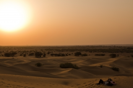 romantic couple looking at the sunset at khuri dunes in thar desert near jaisalmer in rajasthan state in india photo