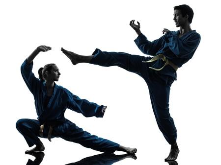 martial arts: una pareja hombre mujer el ejercicio de karate artes marciales vietvodao en el estudio de la silueta aislado en el fondo blanco