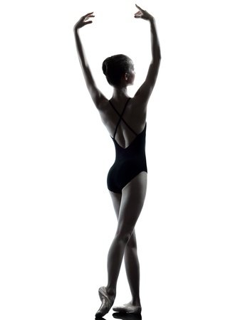 ballet dancing: one caucasian young woman ballerina ballet dancer stretching warming up in silhouette studio on white background Stock Photo