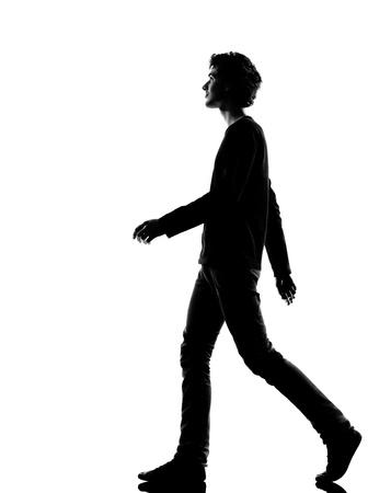 walking alone: silueta joven caminando en el estudio aislado sobre fondo blanco