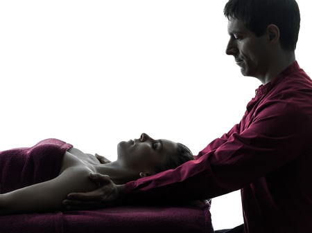 massage table: woman receiving shoulder massage  in silhouette studio on white background Stock Photo