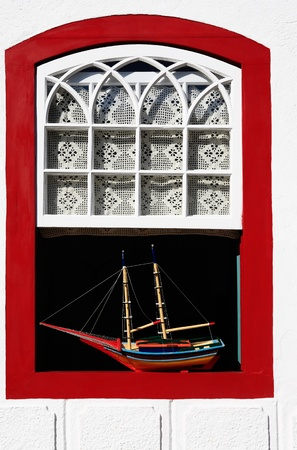 streetscene: boat model at a window of the beautiful portuguese colonial typical town of parati in rio de janeiro state brazil Stock Photo