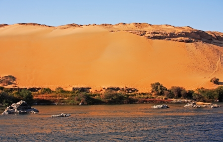 nile river: desert sand dune at sunset with blue sky on the shore of the river nile in egypt