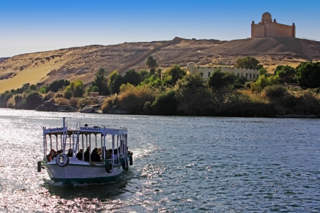 nile river: boat cruising on the river nile with Aga Khan tomb on the shore near aswan in egypt