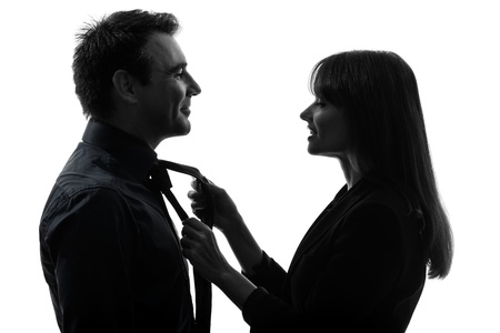 one caucasian couple woman helping man tying  in silhouette studio isolated on white background photo
