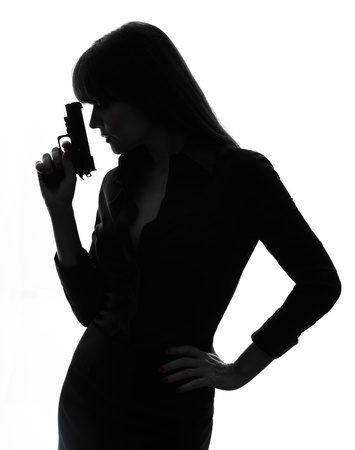 one caucasian sexy detective  woman holding aiming  gun in silhouette studio isolated on white background Stock Photo - 17310937