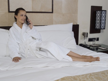 beautiful calm and serene woman in palace hotel room lying on a king size bed phonig photo