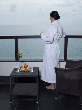 beautiful calm and serene woman in palace hotel room at the balcony facing the sea photo