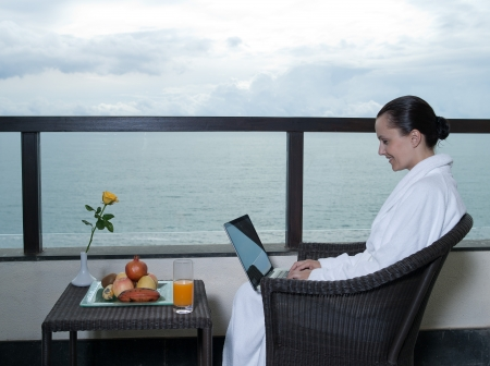 beautiful calm and serene woman in palace hotel room at the balcony facing the sea with a computer laptot photo
