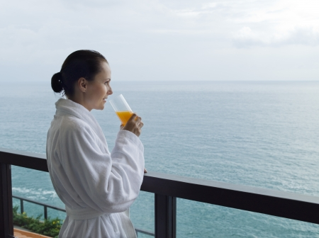 beautiful calm and serene woman in palace hotel room at the balcony facing the sea driking orange juice photo