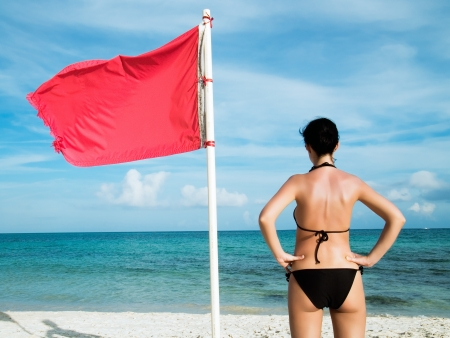 bandera mexicana: mujer de pie en la playa cerca te una señal de alerta sobre el significado del mar que la natación es peligroso y está prohibido Foto de archivo