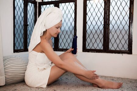 arabic woman: woman relaxing in a spa lounge in india arabic style applying skincare lotion Stock Photo