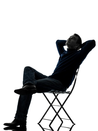 one caucasian man sitting resting looking up  full length in silhouette studio isolated on white background Stock Photo