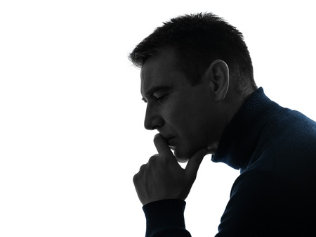 man profile: one caucasian man serious thinking pensive portrait in silhouette studio isolated on white background