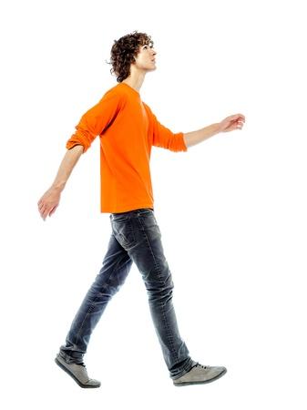 un hombre joven caucásico caminando vista lateral mirando hacia arriba en el estudio de fondo blanco