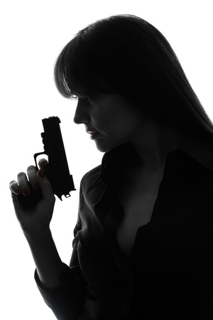 one caucasian sexy detective  woman holding  gun in silhouette studio isolated on white background photo