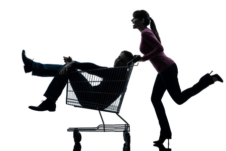 shopping trolleys: one caucasian couple woman  with man sitting in shopping cart   in silhouette studio isolated on white background
