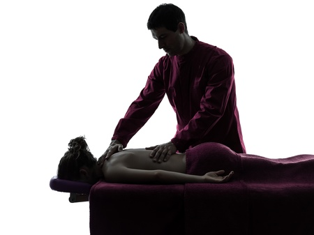 therapist: man woman back massage in silhouette studio on white background