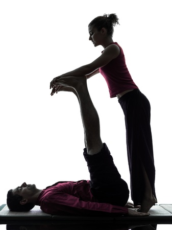 one man and woman perfoming feet legs thai massage in silhouette studio on white background Stock Photo