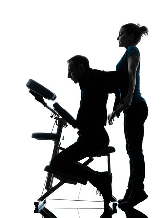 one man and woman perfoming chair back massage in silhouette studio on white background photo