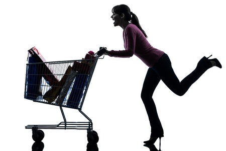 full shopping cart: one caucasian woman with full shopping cart in silhouette studio isolated on white background