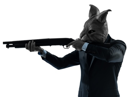 gangster background: one caucasian man rabbit mask hunting with shotgun portrait in silhouette studio isolated on white background Stock Photo