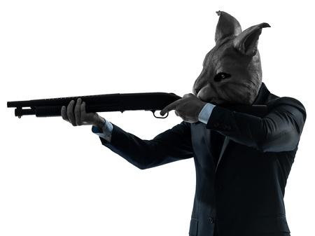 hombre disparando: un hombre caucásico caza del conejo con el retrato de la máscara de escopeta en el estudio de la silueta aislado en el fondo blanco