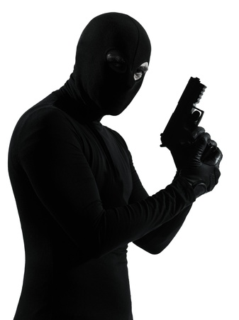 thief criminal terrorist holding gun portrait in silhouette studio isolated on white background photo