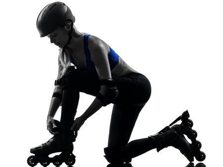 patines: una mujer cauc�sica rusa atar los patines silueta estudio aislado sobre fondo blanco